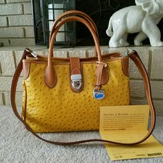 Dooney & Bourke Ostritch Handbag Authentic Dooney & Bourke Ostritch Leather Top Handle in mustard.Registration Card included.Style # is OT51MT if ud like to google for more info.measures 12.6X8 (top-Bottom).Long strap included. No dustbag.i pkg safely.Bag has been used & shouldnt b considered perfect although i c no damage or stains to mention.handles/Strap show a bit of patina n my opinion. Very Clean.True Color is n Web Pic (pic #4/Top right)Willing to Trade. Use offer system only.im also…