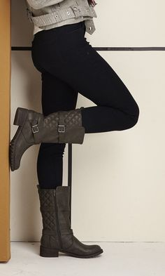 Mid-calf moto boot with a quilted texture, straps, buckles, pull tabs and a lug sole.