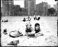 Two young women wearing bathing suits lying on the sand at Oak Street Beach c. 1928.