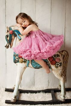 Children & Family Portrait Photography by Jo Frances Wellington - Dreamy photo of young girl resting on vintage rocking horse, by Jo Frances