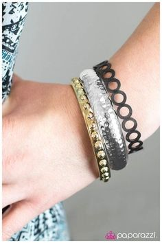 Lollapalooza - Silver  $5.00  Product Description  A trio of gold, silver, and gunmetal bangles stack into a metallic rainbow. A gold bangle decorated with textured studs is paired with a silver bangle with a hammered finish and a gunmetal bangle with a cutout circle pattern.  Sold as one set of three bangles.
