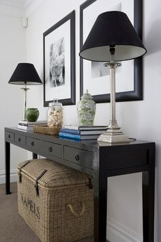Chic foyer features seagrass trunk tucked under black console table with 5 drawers topped with silver lamps accented with black lamp shades, white and green ginger jar, books, seagrass tray and glass canister filled with seashells. Entrance Foyer, Entryway Decor, House Entrance, Black Sofa Table, Console Table Styling, Console Tables, Hall Tables, Side Tables, Lampshade Designs