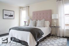 Pink and gray bedroom features a tall pink button tufted headboard on bed dressed in white and gray bedding as well as a dark gray pleated bedskirt atop a gray geometric print rug flanked by round wrought iron bedside tables flanked with windows dressed in white linen curtains.