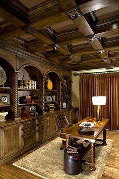 Built-in credenzas with hutches above anchor each side of the room in this amazing golf cart garage-to-library transformation. The unique coffered ceiling with grasscloth inserts sits above the room. The old garage door has been replaced by beautiful French doors leading to a courtyard that was once a paved driveway. Custom design by VM Concept in Scottsdale, AZ.