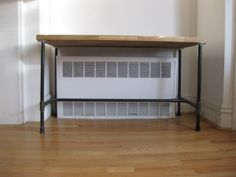 Build your own cheap desk using plumbing pipes and a section of countertop wood.