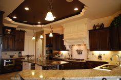 Specialty lighting under, over, rope lights, dropped gas stove top, microwave drawer, 8 ft island, two different kinds of granite, dark popped up ceiling, magnetic knife holder stove back splash, tile on the door entry, vent hood matches the island