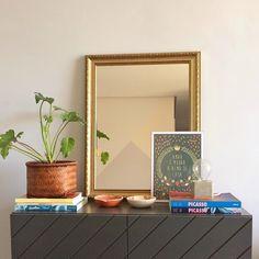 """Há alguns meses colocamos esse buffet da @oppadesign em nossa sala o buffet Portunhol. A gente procurava um móvel que não fosse muito grande mas que pudesse guardar algumas louças e servir de apoio para o nosso espelho. Bingo! Decoramos o buffet com uma Costela De Adão alguns livros e o pôster """"Mudar a Alma"""" no formato A4 (21x30cm).  O espelho reflete o outro lado da sala e revela a parede que pintamos com figuras geométricas e tons pastel.  - Vista a sua casa para 2017…"""