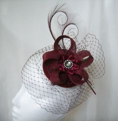 Burgundy Veiled Isadora Percher Fascinator Order Now from www.indigodaisyweddings.co.uk Specialising in stunning bespoke cocktail fascinators and formal hats in a wide range of colours, perfect for Royal Ascot and The Kentucky Derby. Plus all your wedding floral accessories including shoe clips, bandeau veils,vintage flapper bands, feather and flower fascinators, feather fans, fairy wands, wrist corsages, wedding bouquets & buttonholes. Worldwide Delivery. #wedding #fascinator #indigodaisy #