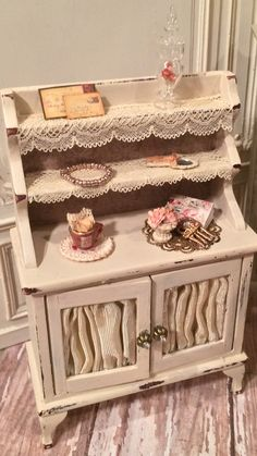 Painted antique distressed cream with French lace doilies draping from each shelf. All items are included. Each one unique with a vintage