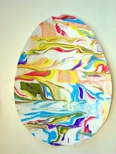 This is sort of an egg shape with all different colors in sort of an abstract or surreal kind of landscape, with a cow like figure & water & appears clouds & sky.    art project