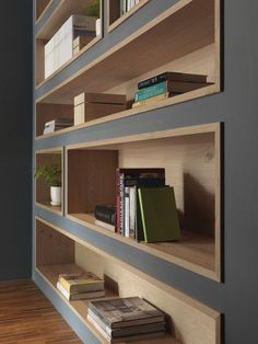 Simple wall of shelving with combination of grey paint and natural wood.