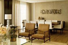 Para o projeto acima, a designer de interiores Cristina Barbara prezou pelo requinte. Os detalhes em dourado, prata e vidro conferem elegância para o ambiente, projetado em variações de marrom. As cortinas em tecido cru são praticamente do mesmo tom das cadeiras da mesa de jantar e do sofá.
