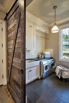 It might be nice to have the barn door on the laundry room, but not have it everywhere. Rustic laundry room featuring a sliding barn door, gray tile floors, stainless steel appliances, white subway tiles and a classic farmhouse sink Rustic Laundry Rooms, Farmhouse Laundry Room, Laundry Room Design, Laundry In Bathroom, Small Laundry, Basement Laundry, Laundry Area, Laundry Decor, Victorian Houses