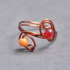 Affordable copper wire wrapped ring with two acrylic beads as the focal point. Can be worn as a regular ring, or a midi ring.