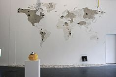 World map made by chipping away gallery wall surface.