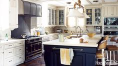 """The owners didn't want a white kitchen, but they want it to be a bright, interesting room — the whole family spends a lot of time here,"" designer Nancy Boszhardt says about her clients with two teenage daughters. To give the Westchester, New York, Tudor personality, she painted the kitchen cabinets a light sand color and the large island a dark midnight blue to help it recede. The hood was designed by architect Radoslav Opacic. Countertops are Jerusalem Gold limestone slab. Custom barstools…"
