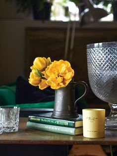 vignette a stacked books, vintage crystal, tulips, and antique pewter in the Sussex home of Nikki Tibbles Grey Candles, Flowers Last Longer, Tulip Dining Table, Winter Flowers, Christmas Flowers, Country House Interior, Yellow Tulips, Floral Artwork, Vintage Sofa
