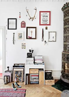 great styling. love the wall display with objects and art, the stunning tiled oven and piles of books and records