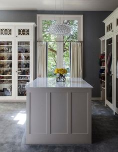 White and gray closet features gray walls lined with glass front wardrobe cabinets filled with shoes and clothes surrounding a white paneled closet island illuminated by a Nuevo Bulle Pendant.