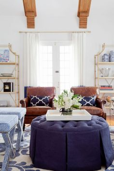 10 Commandments to Designing Your Living Room #theeverygirl   lovely blue and white young trad living room with white walls, white drapes, and brown leather chairs for some oomph