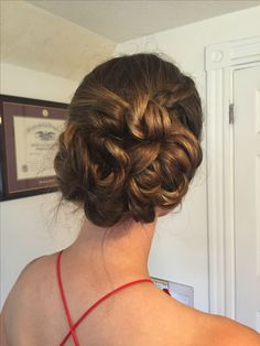 Low side bun updo for wedding guest or bridesmaid hair with side braid and pinned curls
