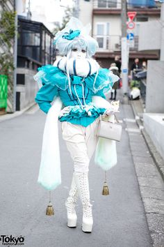 Japanese shironuri artist Minori on the street in Harajuku with a vintage and handmade look features faux fur collar & attached tassel scarf, blue top, lace up platform boots & a small cat. Full Look & Minori's World Documentary