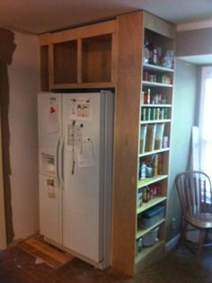 """To expand our kitchen space we tore out the """"pantry closet,"""" moved the fridge into the corner, then built an """"open pantry"""" around the fridge. This makes is easier to access the foods we eat regularly, and store bulky items up top. The thin area on the Left can be used to store wine bottles."""