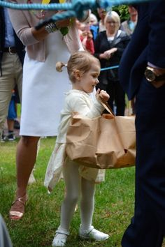 A helpful Swedish little Princess Estelle carries a bag with presents for her mommy dearest during the Victoria Day celebrations at Solliden, 14.07.2014 in Oland, Sweden.