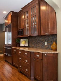 HGTV presents a warm transitional kitchen with dark wood cabinets, a mosaic tile backsplash and stainless steel appliances.