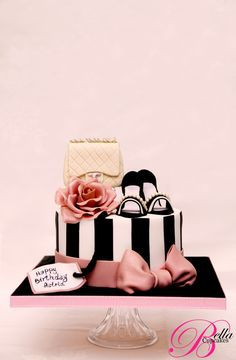 Black and white striped cake with pink bow and sugar flower, purse, and high heels