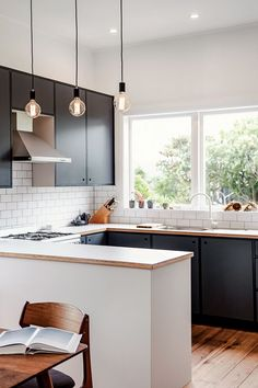 lovely kitchen with black cabinets, wood counter tops, and industrial exposed bulb pendant lights.