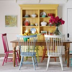 yellow hutch, chairs painted different colors