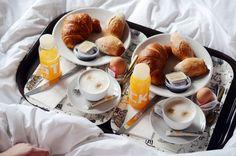 Fancy breakfast in bed with coffee and orange juice on a cute little tray.