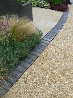 Black riven limestone setts   buff sandstone paving   buff flint gravel