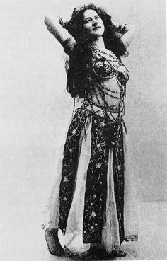 1920s postcard; probably not a bellydancer. Costume is of interest because although I can't vouch for the top, the belt of wide ribbons/ornamented panels does appear in old paintings & some folk attire.