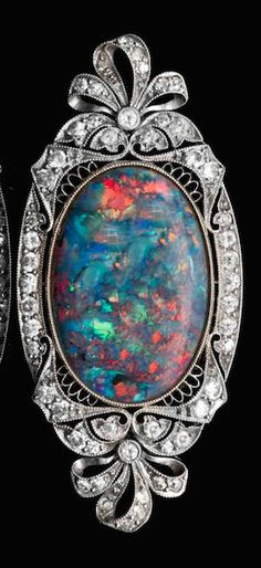 An Edwardian Platinum, Diamond and Black Opal Brooch, containing one oval black opal measuring approximately 21.10 x 14.42 x 3.82 mm within an intricate bow motif filigree surround containing numerous old European and round single cut diamonds weighing approximately 0.75 carat total, white gold pin fittings.