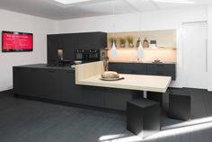 Zwarte keuken met lichte houttinten. Enerzijds zorgt deze donkere keuken in carbon kleur voor een rustgevend effect. Anderzijds zorgen de houttinten die gebruikt worden als werkblad en muurafwerking dan weer voor een helder en warm gevoel. De keukenkasten hebben horizontale, zwarte greepjes die perfect aansluiten bij de deurtjes.
