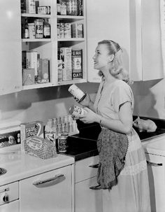 a woman putting cans away in her kitchen cupboard | 1952 |