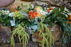 Fireplace decorated with drooping amaranths, dahlias, roses, and hydrangea in white, peach, orange, and green