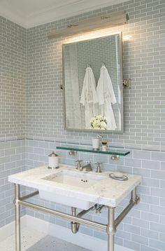source: Mabley Handler  Amazing bathroom with blue glass subway tiles backsplash, polished nickel picture light, rectangular pivot mirror, vintage glass shelf and marble top 2-leg washstand.