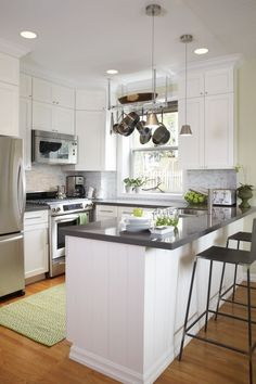 black and white kitchen: gray countertops.  The new Quarella countertop includes an overhang for informal meals. Narrow horizontal Carrara marble tile replaces the plain white backsplash and adds a modern yet classic touch.