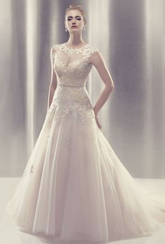 Brides: CB Couture;Non-beaded embroidered lace appliques naturally flow over the illusion jewel neckline and on to the skin. The sheer tulle with lace appliques continue to create cap sleeves with an open keyhole back. Non-beaded, embroidered lace appliques on layers of tulle over satin create this