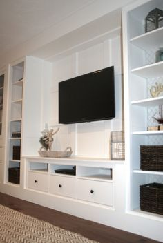 Like this. Open in center for future homework nook. Shelves across top, with opening for TV. Maybe higher cabinets at the bottom too, and pretty countertop above. Space behind to bring cords from tv down to the shelves.