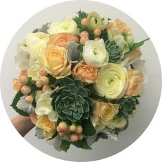 Succulents, hypericum, peach roses, dusty miller and ranunculus