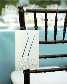 Table numbers hanging on chairs echo the blue-and-eyelet theme at a wedding in Charleston, South Carolina