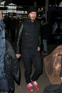 Low key arrival: David Beckham clashed his all-black travelling look with a pair of bright red trainers as he arrived in Paris on Tuesday