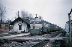 """From Classic Trains: """"New York Central 4505, a rare Fairbanks-Morse CPA-24-5, leads a train toward Chicago at Otis, Indiana, in April 1954. A Studebaker, built in nearby South Bend, is beside the depot."""" Photo by Eugene Van Dusen"""