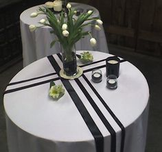 Black ribbon on a white tablecloth, votives filled with black rice, various vessels filled with white flowers designed by Whidbey Party Girls