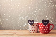 Valentine's day holiday celebration with couple of cups and hearts over bokeh background