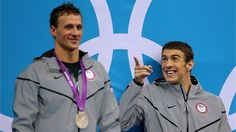 Gold medallist Michael Phelps of the United States reacts whilst waiting the receive his medal alongside Silver medallist Ryan Lochte of the United States on the podium during the Victory Ceremony for the men's 200m Individual Medley final on Day 6